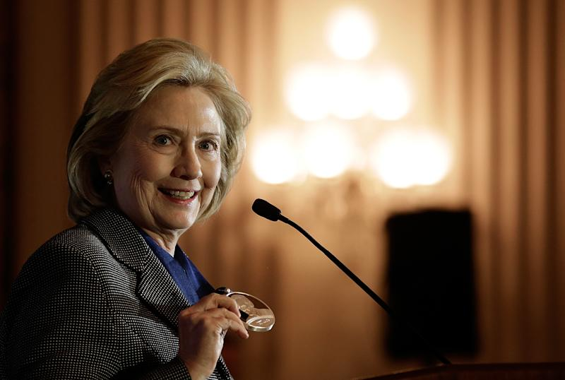 WASHINGTON, DC - DECEMBER 06: While delivering remarks, former U.S. Secretary of State Hillary Clinton displays the 2013 Tom Lantos Human Rights Prize after receiving the award December 6, 2013 in Washington, DC. Clinton received the award for her work in the areas of women's rights and internet freedom. (Photo by Win McNamee/Getty Images)