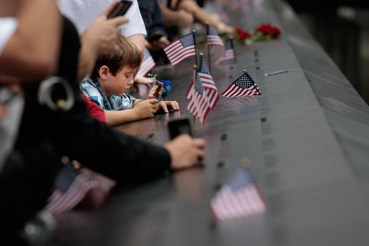 NEW YORK, NY - SEPTEMBER 11:  Family members of the victims of the September 11 terror attacks stand at the perimeter of the 9/11 Memorial South Pool during the tenth anniversary ceremonies of the September 11, 2001 terrorist attacks at the World Trade Center site, September 11, 2011 in New York City. New York City and the nation are commemorating the tenth anniversary of the terrorist attacks which resulted in the deaths of nearly 3,000 people after two hijacked planes crashed into the World Trade Center, one into the Pentagon in Arlington, Virginia and one crash landed in Shanksville, Pennsylvania. (Photo by Chip Somodevilla/Getty Images)