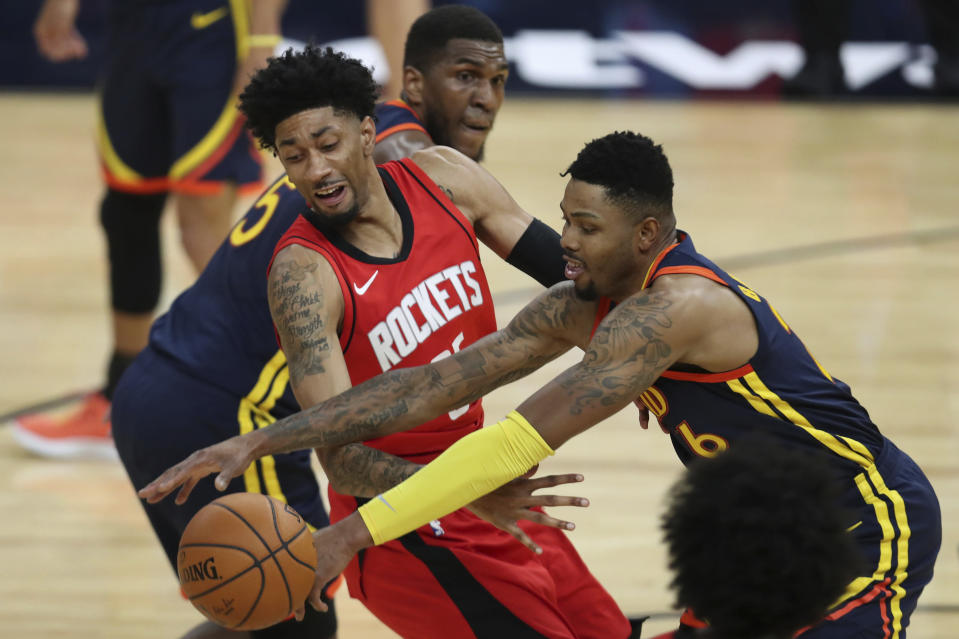 Golden State Warriors guard Kent Bazemore, right, reaches for the ball next to Houston Rockets forward Christian Wood during the first half of an NBA basketball game in San Francisco, Saturday, April 10, 2021. (AP Photo/Jed Jacobsohn)