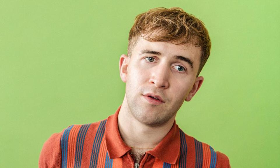 It's A Sin: Callum Scott Howell wearing an orange striped zip-up polo against a green background