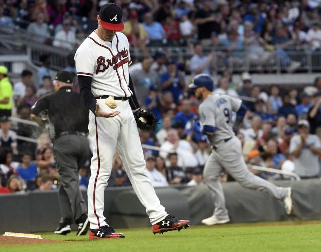 Atlanta Braves pitcher Mike Foltynewicz, foreground, tosses the rosin bag as Los Angeles Dodgers' Yasmani Grandal, back right, approaches third base while running bases during his home run in the third inning of a baseball game Friday, July 27, 2018, in Atlanta. (AP Photo/John Amis)