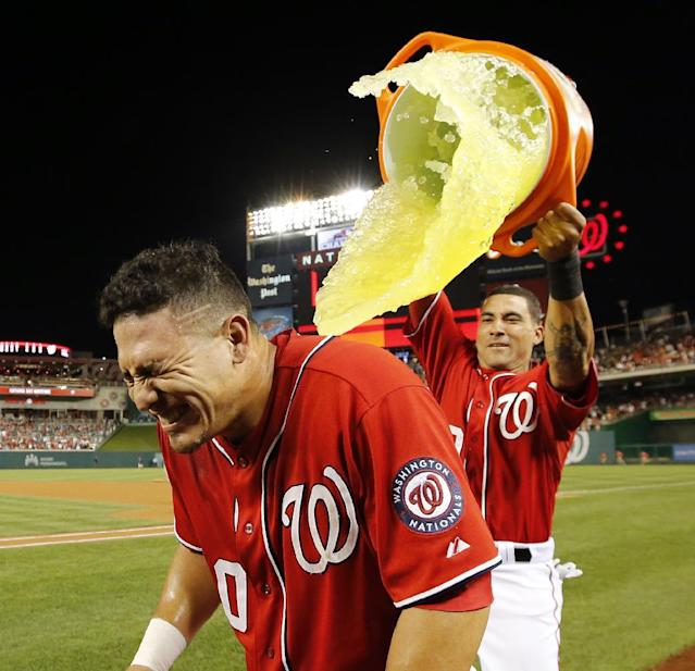 Washington Nationals' Wilson Ramos gets dunked by Ian Desmond after a baseball game against the Pittsburgh Pirates at Nationals Park, Saturday, Aug. 16, 2014, in Washington. Ramos hit the game-winner to score Bryce Harper. The Nationals won 4-3. (AP Photo/Alex Brandon)