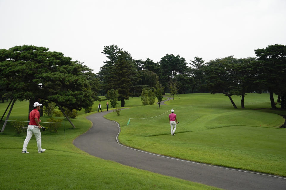 FILE - IN this Aug. 16, 2019, file photo, two golfers walk across the course during a test event at Kasumigaseki Country Club in Kawagoe, Japan, near Tokyo. Kasumigaseki is regarded as the most famous course in Japan. It opened in 1929 and features 36 holes for members. It hosted the precursor to the World Cup in 1957, which Japan won over the U.S. team of Jimmy Demaret and Sam Snead. (AP Photo/Jae C. Hong)
