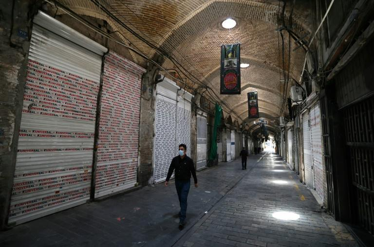 Iranians walk past stores closed by Covid restrictions in the Tehran Bazaar in the heart of the capital