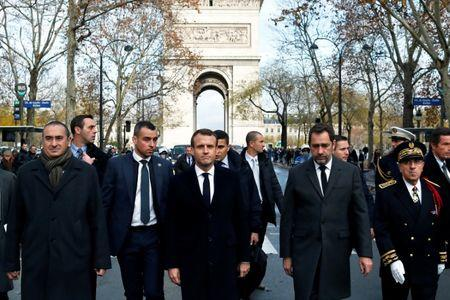 Macron on a visit to the riot-battered neighbourhood around the Arc de Triomphe in Paris
