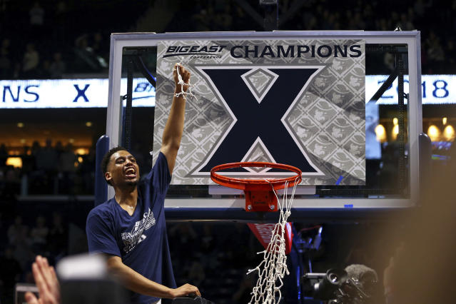 Trevon Bluiett holds up a piece of net after Xavier clinched its first Big East regular-season championship. (AP)