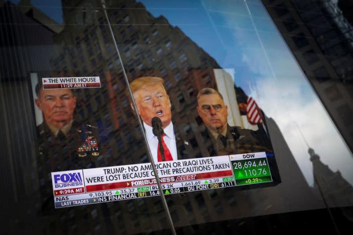 U.S. President Donald Trump is seen on a screen reflected in a window as he delivers a statement from the White House in New York