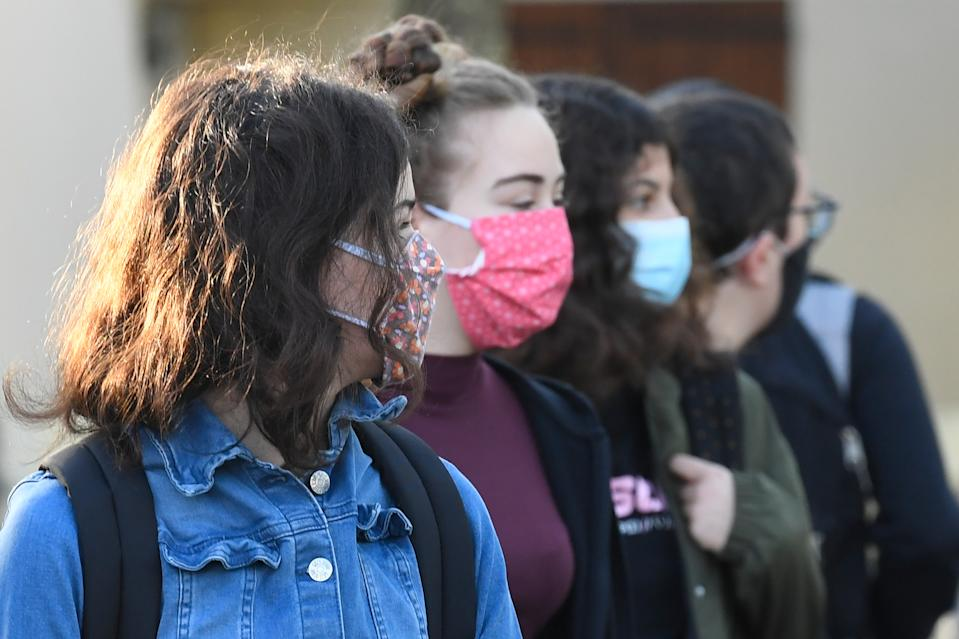 Schoolchildren wearing protective face masks wait to enter in Claude Debussy college in Angers, western France, on May 18, 2020 after France eased lockdown measures to curb the spread of the COVID-19 pandemic, caused by the novel coronavirus. -  (Photo by Damien MEYER / AFP) (Photo by DAMIEN MEYER/AFP via Getty Images)