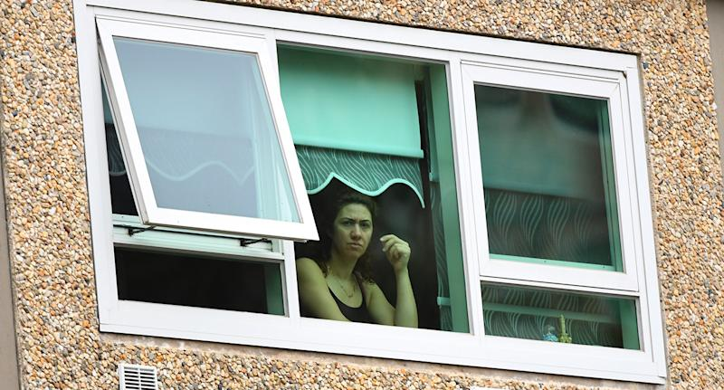 A woman looks out from a window inside a unit at the public housing tower along Racecourse Road in Melbourne. Source: AAP