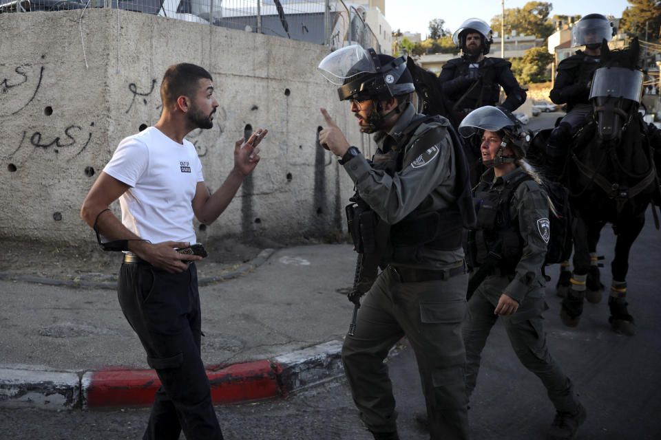 An Israeli Arab man argues with Israeli border police officer during a protest in the Sheikh Jarrah neighborhood of east Jerusalem, where several Palestinian families are under imminent threat of forcible eviction from their homes, Saturday, May 15, 2021. (AP Photo/Mahmoud Illean)