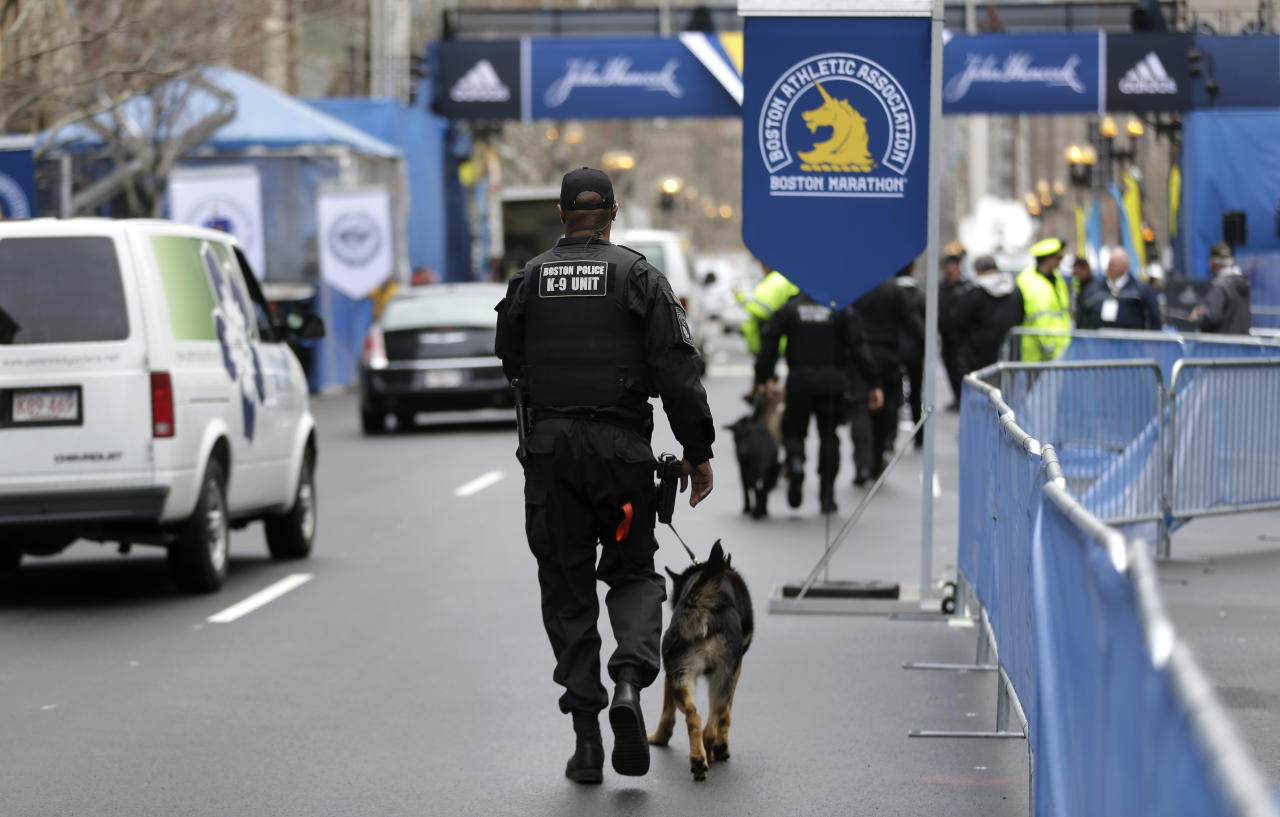 A law enforcement official patrols the area with a dog near the finish line of the Boston Marathon, Tuesday, April 15, 2014, in Boston. Vice President Joe Biden is expected to be among the dignitaries Tuesday during ceremonies to honor victims, and the first responders, doctors and nurses who helped them, following the April 15, 2013, bombings, during a tribute at the Hynes Convention Center in Boston. (AP Photo/Steven Senne)