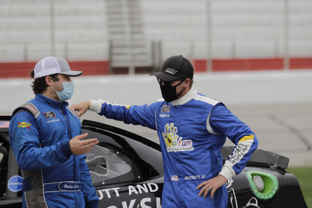 Bayley Currey, left, and Ronnie Bassett Jr., right, talk in pit row before a NASCAR Xfinity Series auto race at Atlanta Motor Speedway, Saturday, June 6, 2020, in Hampton, Ga. (AP Photo/Brynn Anderson)