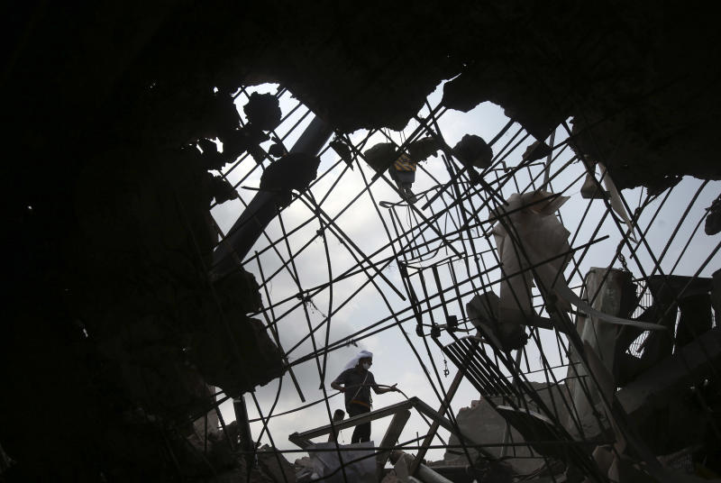 A worker is seen through a broken cement wall as he toils in the collapsed garment factory building in search for bodies on Thursday, May 2, 2013, in Savar, near Dhaka, Bangladesh. Rescuers found more bodies in the concrete debris of the collapsed garment factory building Thursday and authorities say it may take another five days to clear the rubble. In addition to the 430 confirmed dead, police report another 149 people are still missing in what has become the worst disaster for Bangladesh's $20 billion-a-year garment industry that supplies global retailers. (AP Photo/Wong Maye-E)