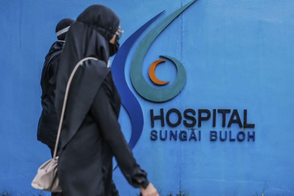 Doctors clad in black are seen outside the Sungai Buloh Hospital during a strike July 26, 2021. — Picture by Hari Anggara