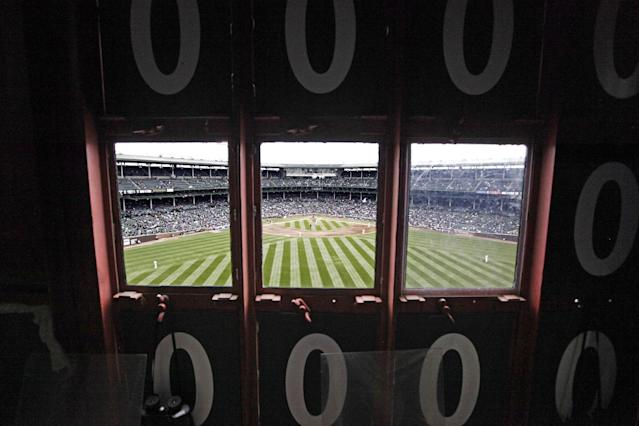 This April 10, 2014 photo shows a view of the field from inside Wrigley Field's iconic scoreboard during a baseball game between Pittsburgh Pirates and Chicago Cubs, in Chicago. With Boston's Fenway Park and Wrigley the only two stadiums in the majors with primary manual scoreboards, it has been a job largely shrouded in mystery until the Cubs allowed The Associated Press climb the steel ladder through the steel floor of the scoreboard for a rare visit to mark Wrigley's 100-year anniversary. (AP Photo/Kiichiro Sato)