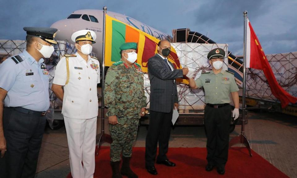 Wan Dong (right), defence attache of the Chinese Embassy to Sri Lanka, and Kamal Gunaratne (second right), Sri Lankan defence secretary general, bump fists at the handover of a batch of Sinopharm vaccine.
