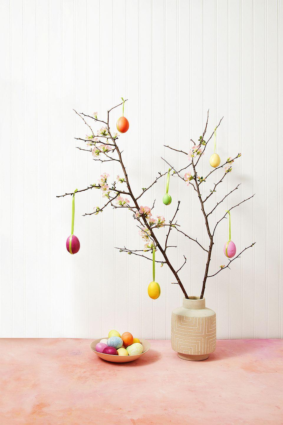 """<p>Gather sturdy branches from your yard or local florist. We used flowering quince branches but you can use pussy willow, forsythia, cherry blossom, magnolia, and dogwood. Place the branches in a heavy vase. </p><p>Gather blown out eggs or lightweight faux craft eggs. Cut a 20-inch piece of thin ribbon. Using hot glue, attach the bottom of the egg to the midpoint of the ribbon. Wrap the ribbon around the egg and attach to the top of the egg with hot glue. Once dry, tie the eggs onto the branches and trim excess ribbon.</p><p><a class=""""link rapid-noclick-resp"""" href=""""https://www.amazon.com/Juvale-48-Count-Plastic-Easter-Eggs/dp/B071NTSY55/?tag=syn-yahoo-20&ascsubtag=%5Bartid%7C10055.g.2217%5Bsrc%7Cyahoo-us"""" rel=""""nofollow noopener"""" target=""""_blank"""" data-ylk=""""slk:BUY CRAFT EGGS"""">BUY CRAFT EGGS</a></p><p><strong>RELATED</strong>: <a href=""""https://www.goodhousekeeping.com/holidays/easter-ideas/g26809936/diy-easter-tree-ideas/"""" rel=""""nofollow noopener"""" target=""""_blank"""" data-ylk=""""slk:How to Get Your Easter Egg Tree to Make a Statement This Spring"""" class=""""link rapid-noclick-resp"""">How to Get Your Easter Egg Tree to Make a Statement This Spring</a></p>"""