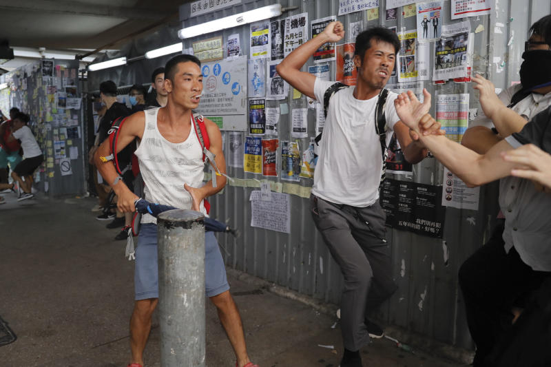 Pro-China supporters, in white, fight with anti-government protesters at the Kowloon Bay district in Hong Kong, Saturday, Sept. 14, 2019. The clashes came after several nights of peaceful rallies that featured mass singing at shopping malls by supporters of the months-long protests demanding democratic reforms. (AP Photo/Kin Cheung)