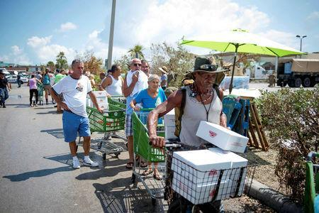 Marines and Sailors with the 26th Marine Expeditionary Unit help distribute food, water, and supplies in support of the Federal Emergency Management Agency in the aftermath of Hurricane Irma as citizens raise a flag at a distribution point in Key West, Florida, U.S. September 14, 2017. U.S. Marine Corps/Cpl. Jon Sosner/Handout via REUTERS
