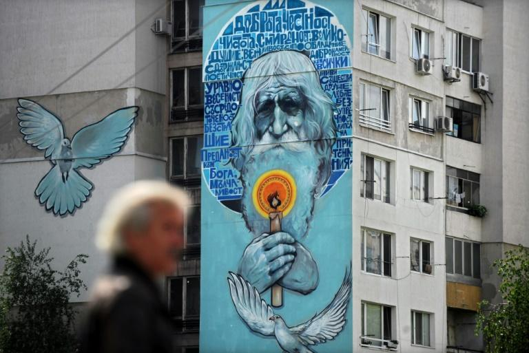 Street artists painted a huge image of the white-haired man holding a candle on the facade of an apartment building in Sofia