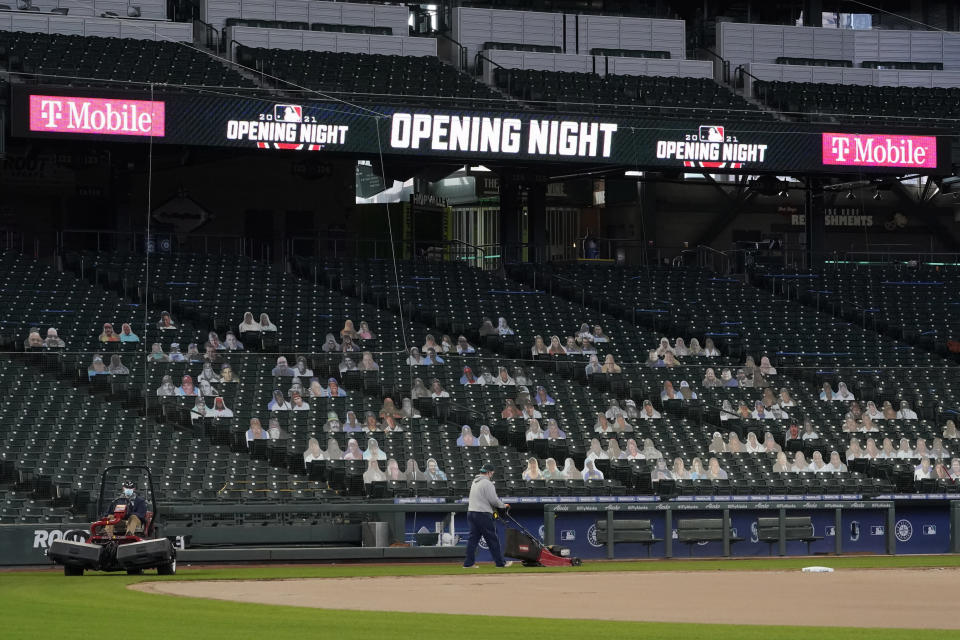 """Grounds crew workers mow near the first-base foul line at T-Mobile Park, the home of the Seattle Mariners baseball team, Monday, March 22, 2021, in Seattle as photos in the stands demonstrate how fans attending reduced-capacity games will be separated into """"seating pods"""" to avoid the spread of COVID-19. The Mariners are scheduled host the San Francisco Giants on April 1 in the Mariners' home-opener. (AP Photo/Ted S. Warren)"""