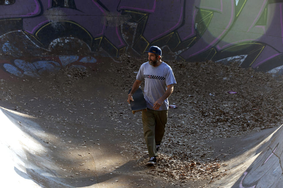 Skateboarder Dallas Oberholzer, 46, walks with his skateboard at at the Germiston Lake Skateboard Park, near Johannesburg, Saturday, July 3, 2021. The age-range of competitors in skateboarding's Olympic debut at the Tokyo Games is remarkably broad and Oberholzer will go wheel-to-wheel with skaters less than half his age. (AP Photo/Denis Farrell)