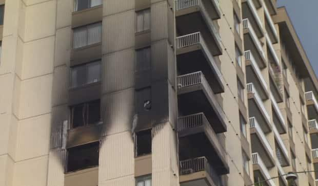 Firefighters say flames were shooting out the windows of a 14th-floor apartment when they arrived.