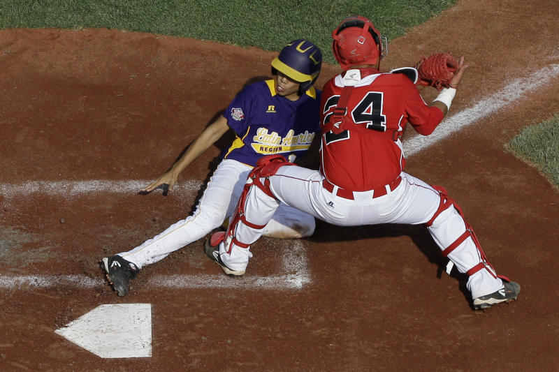 Aguadulce, Panama's Jean Mar Sanchez, left, scores past the tag from Tijuana, Mexico's Saul Favela on a sacrifice fly by Jordan Agrazal during the second inning of an elimination baseball game at the Little League World Series tournament on Thursday, Aug. 22, 2013, in South Williamsport, Pa. (AP Photo/Matt Slocum)