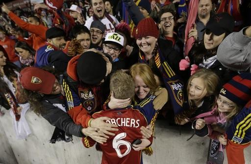 ADVANCE FOR WEEKEND EDITIONS, JULY 4-6 - FILE - In this Nov. 7, 2013 file photo, fans hug Real Salt Lake defender Nat Borchers (6) after Real Salt Lake defeated the Los Angeles Galaxy in the second leg of the MLS Western Conference semifinal, in Sandy, Utah. Major League Soccer is growing, with more lucrative TV and sponsorship deals and greater attendance. But it hasn't yet translated into a television ratings breakthrough, and the league hopes the World Cup provides a long-lasting boost. (AP Photo/Rick Bowmer, File)