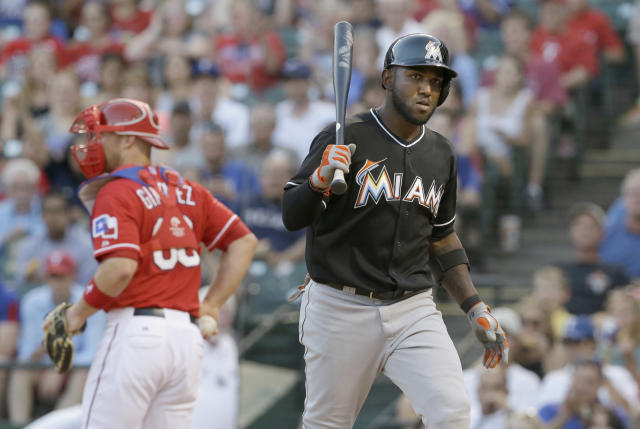 Miami Marlins Marcell Ozuna, right, heads back to the dugout after striking out against the Texas Rangers during the fourth inning of a baseball game in Arlington, Texas, Wednesday, June 11, 2014. (AP Photo/LM Otero)