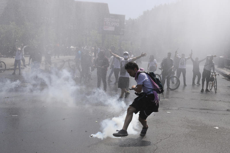 A protester kicks a tear gas canister during clashes with police in Santiago, Chile, Sunday, Oct. 20, 2019. Protests in the country have spilled over into a new day, even after President Sebastian Pinera cancelled the subway fare hike that prompted massive and violent demonstrations. (AP Photo/Esteban Felix)
