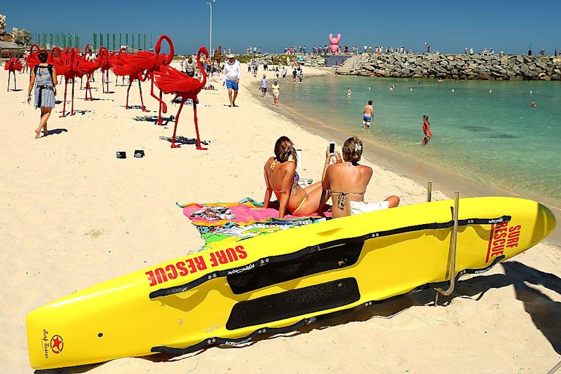 Pictured is two women sunbathing at Perth's Cottesloe beach.