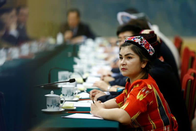FILE PHOTO: A delegate wearing a traditional costume attends a session of the Xinjiang Uyghur Autonomous Region on the sidelines of the National People's Congress in Beijing