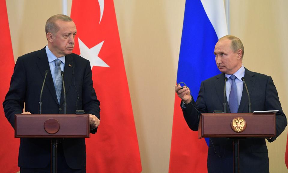 Russian President Vladimir Putin, right, and Turkish President Recep Tayyip Erdogan look at each other during a joint news conference after their talks in the Bocharov Ruchei residence in the Black Sea resort of Sochi, Russia, Tuesday, Oct. 22, 2019. Erdogan says Turkey and Russia have reached a deal in which Syrian Kurdish fighters will move 30 kilometers (18 miles) away from a border area in northeast Syria within 150 hours. (Alexei Druzhinin/Sputnik Kremlin Pool Photo via AP)