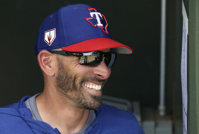 FILE - In this March 6, 2019, file photo, Texas Rangers manager Chris Woodward smiles as he talks with other coaches prior to a spring training baseball game against the San Francisco Giants, in Surprise, Ariz. First-year Texas manager Chris Woodward loves that the expectations are higher. At 42-36 just shy of the midpoint of the season, the Rangers havent lost any of their eight series over the past month. (AP Photo/Ross D. Franklin, File)