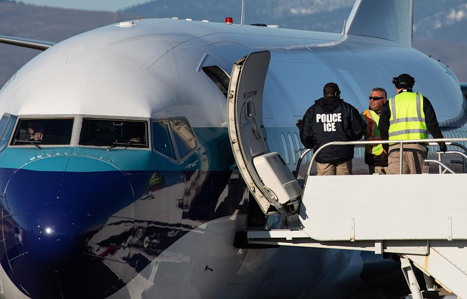 Agents working for U.S. Immigration and Customs Enforcement prepare to board detainees onto a flight in February. (Photo: David Ryder/Getty Images)