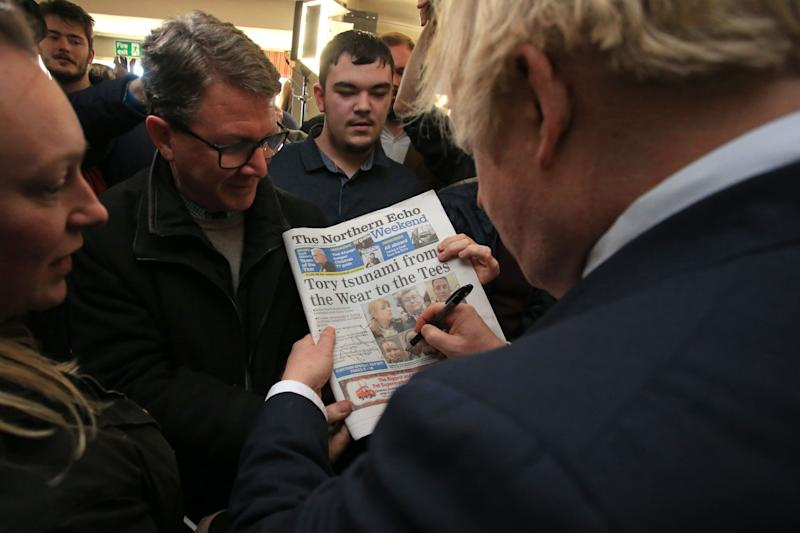 Britain's Prime Minister Boris Johnson signs a copy of The Northern Echo for a supporter during a visit to see newly elected Conservative party MP for Sedgefield, Paul Howell at Sedgefield Cricket Club in County Durham, north east England on December 14, 2019, following his Conservative party's general election victory. - Prime Minister Boris Johnson called on Britons to put years of bitter divisions over the country's EU membership behind them as he vowed to use his resounding election victory to finally deliver Brexit next month. (Photo by Lindsey Parnaby / POOL / AFP) (Photo by LINDSEY PARNABY/POOL/AFP via Getty Images)