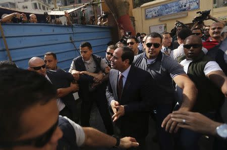 Presidential candidate Sisi arrives with his bodyguards at a polling station to cast his vote during the presidential election in Cairo