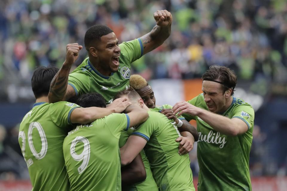 In this photo taken Nov. 10, 2019, Seattle Sounders defender Roman Torres holds up his arms as he celebrates with teammates after defender Kelvin Leerdam scored a deflected goal against Toronto FC during the second half of the MLS Cup championship soccer match in Seattle. Seattle's championship victory was among Washington state's top news stories of 2019. (AP Photo/Ted S. Warren)