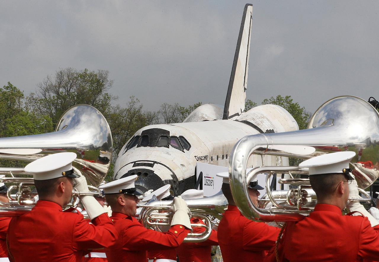 A military band plays as the the Space Shuttle Discovery is towed up to an event at the Smithsonian National Air and Space Museum Steven F. Udvar-Hazy Center April 19, 2012 in Chantilly, Virginia. The space shuttle Discovery is the he oldest and most traveled vehicle from NASA's space shuttle program, and will replace the Interprise at the museum.  (Photo by Mark Wilson/Getty Images)