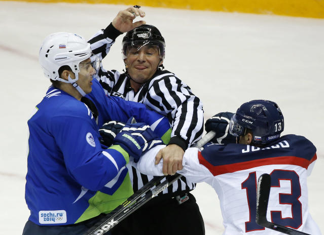 A linesman breaks up a fight between Slovenia defenseman Ziga Pavlin, left, and Slovakia forward Tomas Jurco period of a men's ice hockey game at the 2014 Winter Olympics, Saturday, Feb. 15, 2014, in Sochi, Russia. (AP Photo/Mark Humphrey)
