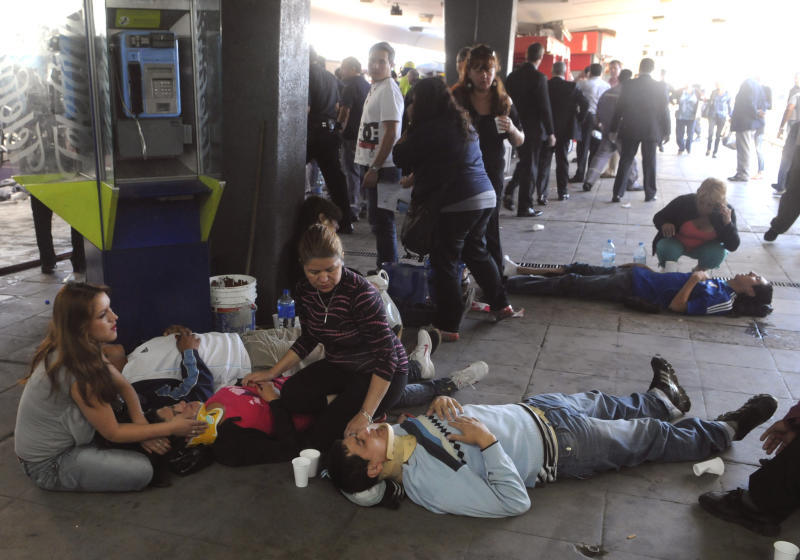 Injured passengers from a commuter train wait to be carried away after a collision in Buenos Aires, Argentina, Wednesday Feb. 22, 2012. A packed train slammed into the end of the line in Buenos Aires' busy Once station Wednesday, killing dozens and injuring hundreds, according to police. (AP Photo/Leonardo Zavattaro,Telam)