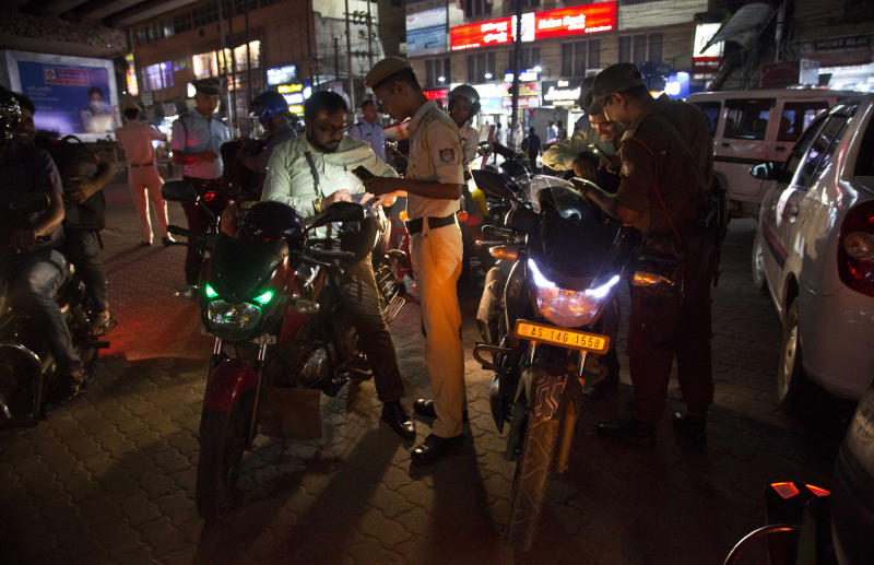 Police personnel check vehicles after a grenade attack in Gauhati, India, Wednesday, May 15, 2019. A grenade lobbed from a motorcycle at a police checkpoint in the heart of a northeastern Indian city injured 10 people on Wednesday in an attack immediately claimed by a separatist leader. (AP Photo/Anupam Nath)