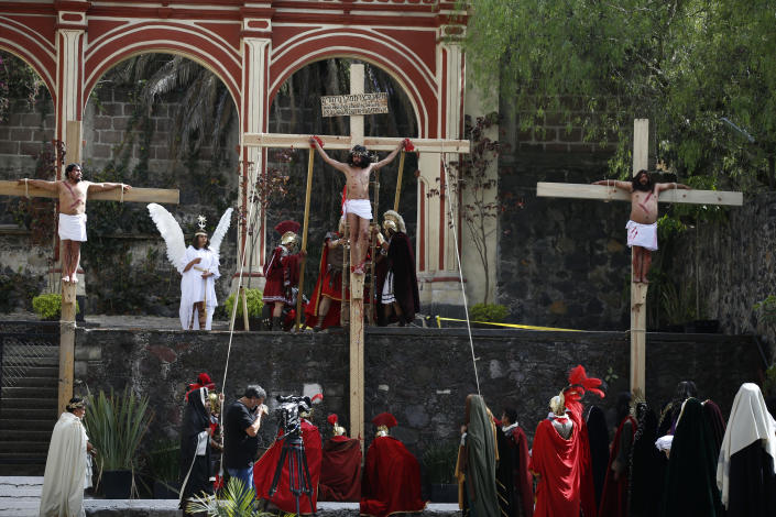 Brando Neri Luna, center, and other cast members reenact the crucifixion of Jesus Christ in the Passion Play of Iztapalapa, outside the Cathedral, on the outskirts of Mexico City, Friday, April 2, 2021, amid the new coronavirus pandemic. To help prevent the spread of the COVID-19, Latin America's most famous re-enactment of the crucifixion of Christ was closed to the public and transmitted live so people could watch at home, for a second consecutive year. (AP Photo/Marco Ugarte)