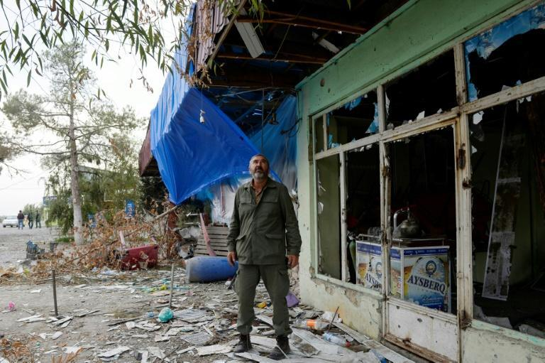 Local resident Rovshan stands by a cafe demaged by shelling in the settlement of Dord Yol in Azerbaijan's Tartar district
