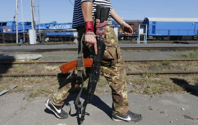 """A pro-Russian separatist walks along a railroad station in the eastern Ukrainian town of Ilovaysk August 31, 2014. Russian President Vladimir Putin called on Sunday for immediate talks on """"statehood"""" for southern and eastern Ukraine, although his spokesman said this did not mean Moscow now endorsed rebel calls for independence for territory they have seized. REUTERS/Maxim Shemetov (RUSSIA - Tags: POLITICS CIVIL UNREST CONFLICT TPX IMAGES OF THE DAY)"""