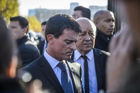 French Prime Minister Manuel Valls (L) and French Defense Minister Jean-Yves Le Drian react as they speak to journalists after they visited the psychological help center at the Ecole Militaire to assist survivors and the families of victims in Paris, France, November 15, 2015, two days after a series of fatal shootings in the French capital. REUTERS/Christophe Petit Tesson/Pool
