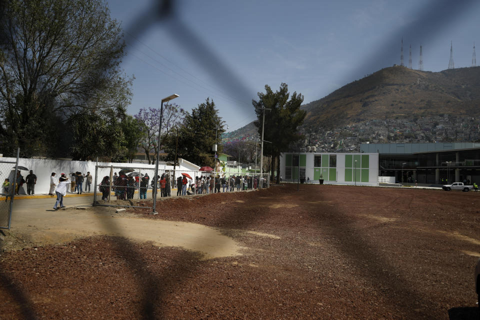 Residents wait in line for a chance to try out a new public transit system dubbed the Cablebus, outside the Campos Revolucion station in the Cuautepec neighborhood of northern Mexico City, Thursday, March 4, 2021. For the residents of Cuautepec, this new system, the first of four planned lines, will turn a commute to the nearest subway station, that can last up to two hours, into a 30-minute ride. (AP Photo/Rebecca Blackwell)