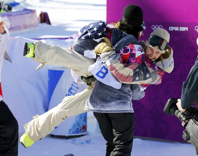 Second-placed Norway's Staale Sandbech carries winner Sage Kotsenburg of the U.S (top) as they celebrate after the men's snowboard slopestyle final at the 2014 Sochi Olympic Games in Rosa Khutor February 8, 2014. REUTERS/Mike Blake (RUSSIA - Tags: SPORT OLYMPICS TPX IMAGES OF THE DAY SPORT SNOWBOARDING)