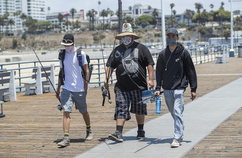SANTA MONICA, CA - JUNE 29: Left to right-Friends Adrian Sanchez, 20, Matthew Gonzalez, 22, and Justice Arreola, arrive at the Santa Monica Pier in Santa Monica to do some fishing. They are all from Santa Monica. L.A. County is expected to reach 100,000 cases of coronavirus. (Mel Melcon / Los Angeles Times)